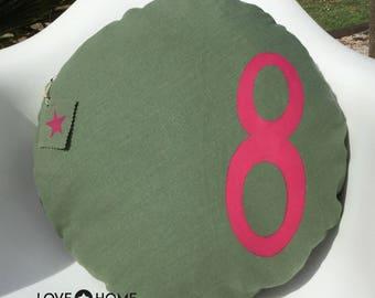 Round cushion in khaki linen with a fuchsia figure