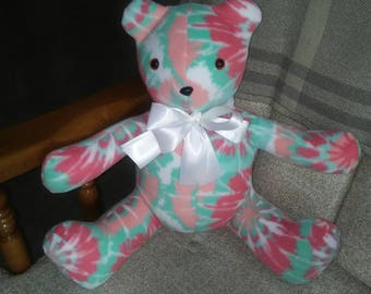 Teddy bear in multicolor fleece.  Safety lock eyes n nose. Hypoallergenic stuffing. Measures 19 inches long. Great nursery addition.