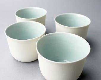 four translucent cups, ocean glaze inside