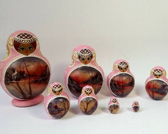 Set of eight vintage Russian dolls in pink,  signed by Ceprueb Nocag, pot bellied style with winter landscape, wooden matroyshka,
