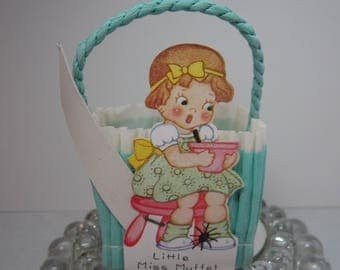 Vintage 1930's blue and white crepe paper nut candy cup party favor basket with die cut image of Little Miss Muffet nursery rhyme character