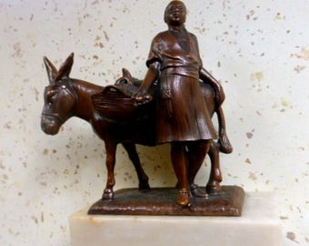 Cast bronze figure of a Arab man with a donkey and fruit baskets