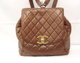 Vintage CHANEL quilted brown lamb leather backpack with gold chain strap and large CC closure. Classic and popular bag.