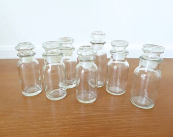 Seven vintage glass spice or apothecary jars with stoppers