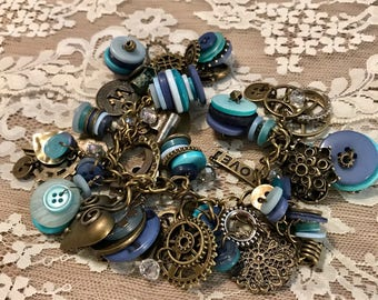Chunky Bracelet Loaded with Buttons And Charms .   Antique Bronze Tone Chain Link Bracelet With Various Shades of Blue Buttons.