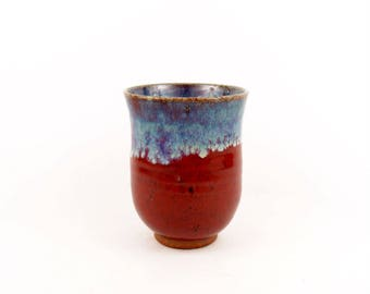 Tea cup in warm raspberry red with purple and cloudy blue glaze around the rim