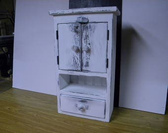 Freestanding / wall hanging primitive distressed cabinet, painted chalk white. two doors and one drawer.