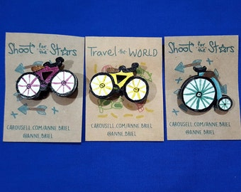 bicycle pin, purple bicycle pin, old bicycle pin, high wheel bicycle, purple bike pin, yellow bike pin, penny-farthing bicycle, blue bicycle