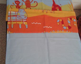 Around baby: bed containing flat sheet + pillowcase matching pattern of the jungle animals