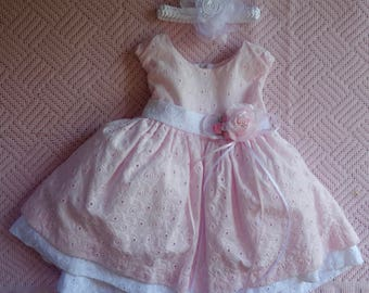 pink and white cotton-like baby dress with removable flower bouquet on waist
