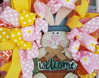 "16"" wire wreath with welcome bunny in pinks, yellow and orange. With mesh"