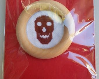 Red skull cross-stitch in a round wooden frame on a card