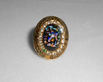 glorious deco ring with multicolor confetti stone on black background with glittery halo ... 1910 to 1930, size 6 to 6.25