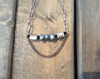 Silver chain necklace adorned with iridescent blue beads