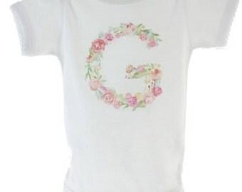 Decorative initial on girls t shirt onesie.