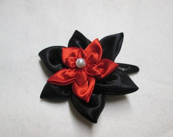 Adorned with a black and Red satin flower hair clip