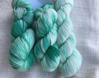 3 skeins of handyed sock yarn with a green to white gradient.