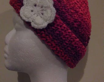 Chunky knit red beanie with flower detail.