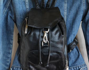 VTG Black leather backpack by Perlina. So dope! With a drawstring and hooked flap closures, it will be your fav summer bag!