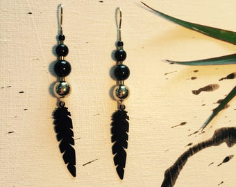 Black/gold earring with feather