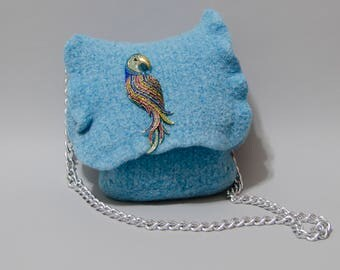 Blue handbag with parrot pin