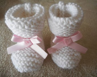 Pink satin bow and white wool baby shoes.
