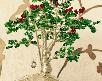 Pearl tree bonsai from silver wire and green leaves and red flowers on the stone