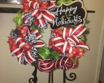 Beautiful evergreen wreath,  and beautiful Christmas ribbon.  It would look beautiful at home, or office.