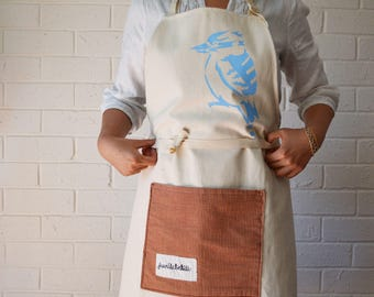 Apron with Blue Kookaburra Screen print and Pocket. Full body thick canvas apron, adjustable tie straps. One size fits all.