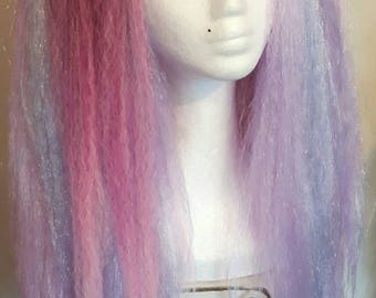 Pair of mixed pinks and light purple hair falls on strong elastic.