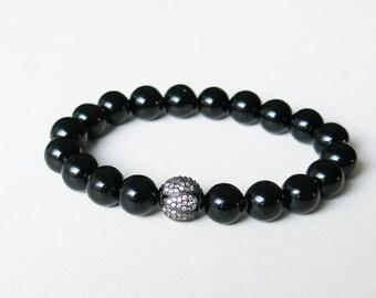 Black onyx bracelet with blackened sterling silver Swarovski crystal focal bead strung on sturdy elastic