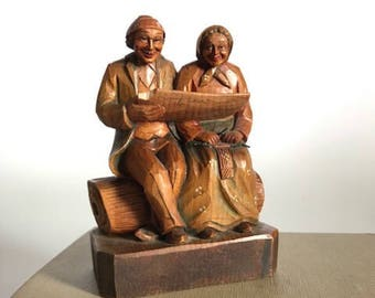 Carved Man and Woman sitting on a log