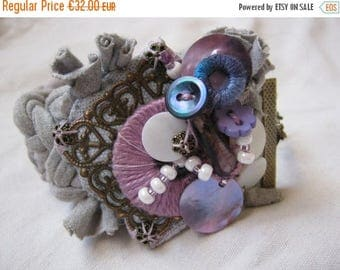 ON SALE Cuff bracelet made of a grey fabric strip, decorated with a filagree, vintage buttons, charms made out of shells or covered cotton,