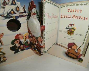 "Vintage Christmas child's pop up book book ""Santa's little helpers "" book Great colorful graphics Santa sleigh reindeer snowman elves & more"