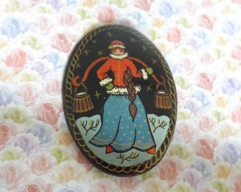 A superb Russian hand painted vintage jewelry brooch decorated in oil paints showing a milk maid in traditional Russian costume