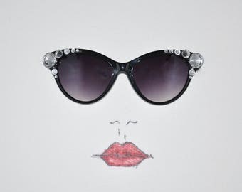 Black Designer fashion cat-eye sunglasses embellished with crystal rhinestone jewels and silvertone accents.