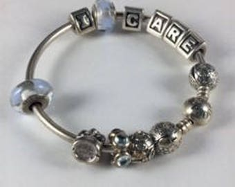 Pandora Sterling Silver Charm Bangle I CARE Letter Beads, Clear Star and Clear Stone Spacers, Silver Drama Mask, and Elaborate Round Beads
