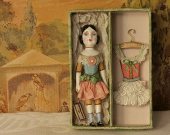 1/12th scale model of a toy doll in a box with separate dress