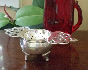 Silver Plated Tea Strainer with Reticulated Handles and  Silver Plated Footed Base.