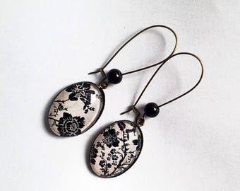 Hanging, bronze earrings, cabochons ovals, black flowers on beige bottom, black pearls.