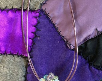 2 strands of grape leather with central multi-bead crystal bead in purple and turquoise
