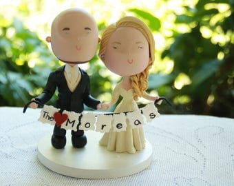 Couple holding hands with banner. Wedding cake topper. Wedding figurine. Bride and Groom. Handmade. Fully customizable. Unique keepsake