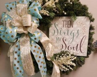 "24"" artificial evergreen wreath with metal  religious sign.  teal and white/gold ribbon"