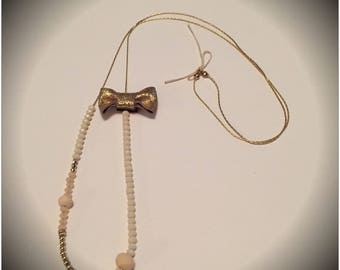 Necklace with beads and leather bow. Gold and beige rose