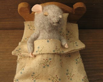 mouse sleeps in its bed with a needle felting