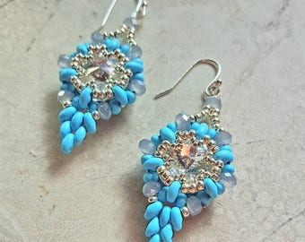 Beautiful swarovski crystal earrings with blue turquoise superduos. They measure 2 niches long.