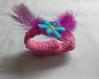 Pink bracelet crocheted from recycled plastic bags customized with a flower and feathers, upcycling