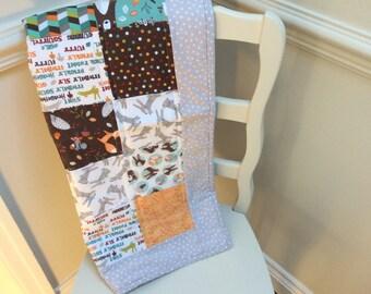 Patchwork pushchair quilt, pram quilt, stroller quilt, car quilt, travel quilt, baby quilt in woodland pattern in orange brown and blue.