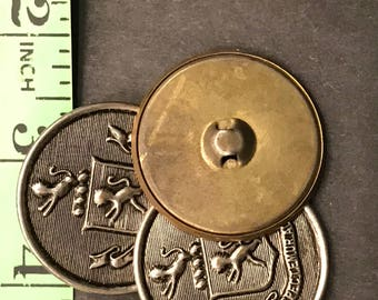"""Three 1-1/2""""metal coat of arms buttons.  2 are silver, 1 copper."""