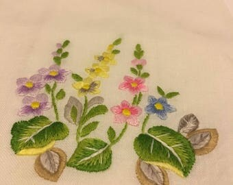 """Embroidered purple, yellow, pink and blue flowers adorn this linen towel. Measures 20""""high x 14""""wide."""